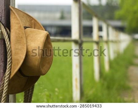 Cowboy hat and lasso on fence American Horse ranch background