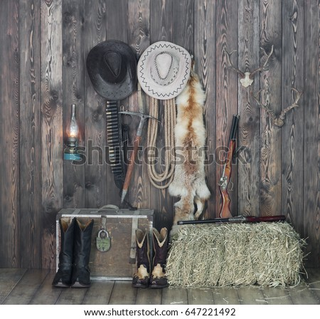 Cowboy hat, boots and weapons on the background of the old barn.Wild west, cowboy,Vintage