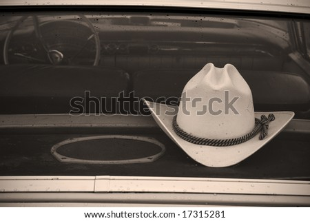 cowboy hat in car, with raindrops on rear window