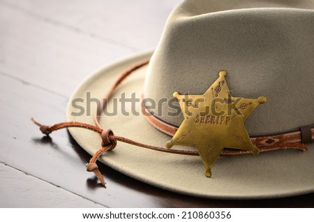 Cowboy hat with Sheriff badge on wooden background in horizontal format with selective focus