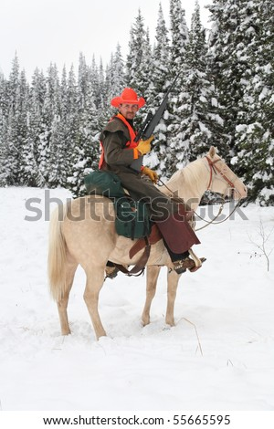 cowboy hunter riding white horse in snow hunting with rifle