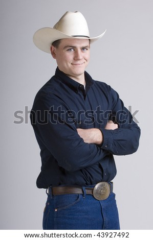 Cowboy in studio with his saddle, chaps, and bridle