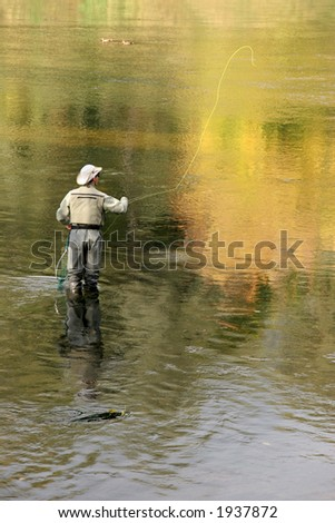cowboy-look flyfisher casting in autumn river