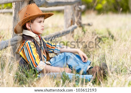 Cowboy on a grass at an old fence