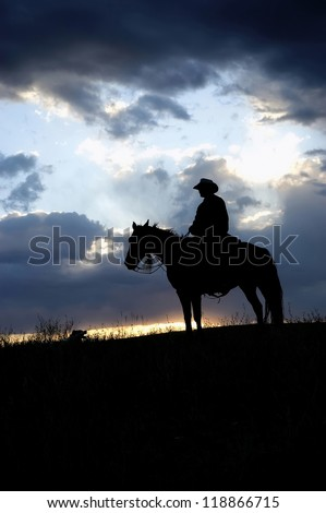 Cowboy,on horseback, silhouetted against dawn sky