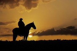 Cowboy, on horseback,silhouetted against the setting sun