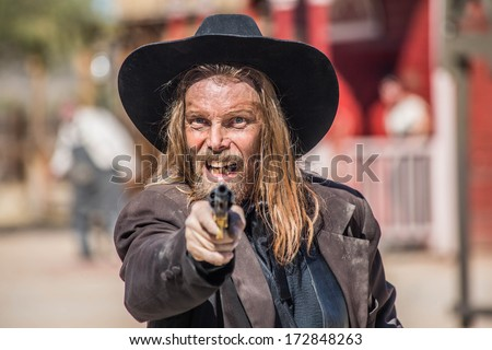 Cowboy Points Gun at You in Town