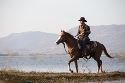 cowboy riding horse in lake against mountain