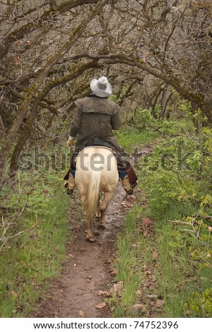 cowboy riding horse on trail through overhanging trees