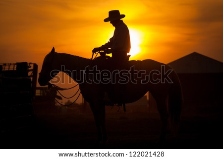 Cowboy silhouette on horse at sunset