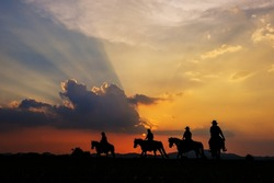 Cowboy silhouette on horseback with mountain view and sunset sky.