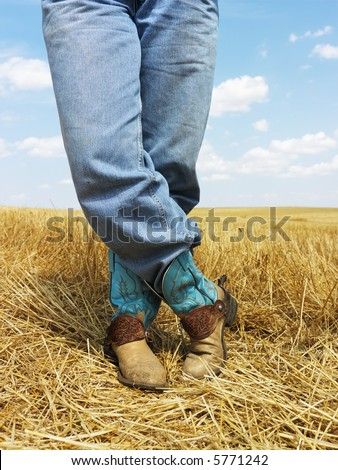 Cowboy standing in harvested crop field wearing funky cowboy boots. - stock photo