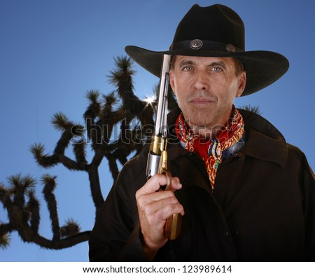 cowboy with gold and silver colored pistol with a joshua tree in the background - stock photo