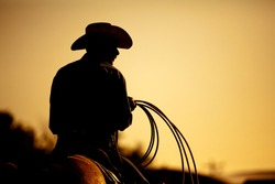 cowboy with lasso silhouette at small-town rodeo. Buyers note: image contains added grain to enhance theme of image.