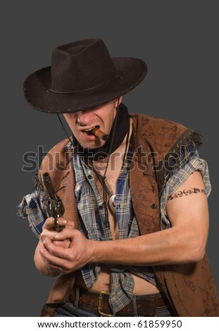 cowboy with revolver isolated on grey background.Shallow DOF - stock photo