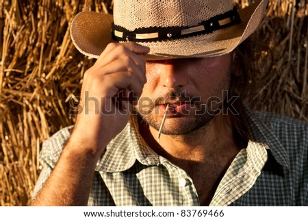 Cowboy with Straw in His Mouth Holding His Hat