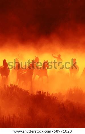 Cowboys chasing wild horses - stock photo