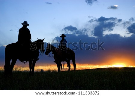 Cowboys on horseback as sun rises