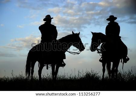 Cowboys,on horseback,silhouetted against a dawn sky