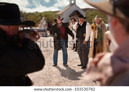 Cowboys pull out their weapons in an old west shoot out