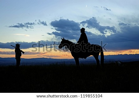Cowboys silhouetted against a dawn Montana sky