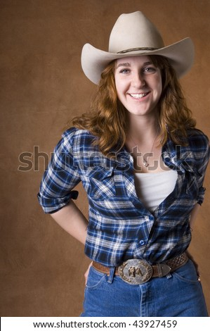 Cowgirl in studio with hat, jeans, and chaps