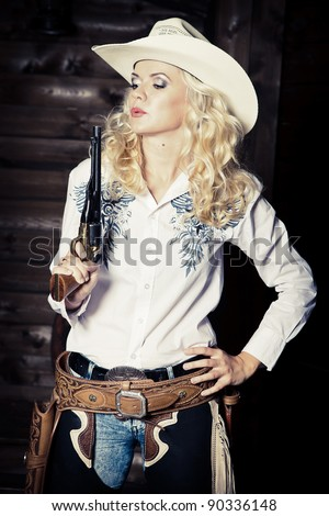 Cowgirl in the stables at the ranch - stock photo