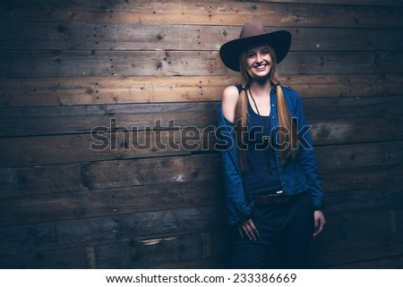 Cowgirl jeans fashion woman with long blonde hair. Standing against wooden wall. #233386669