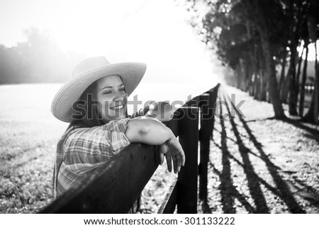 8137c8040d3 Cowgirl lady woman female wearing cowboy hat and flannel shirt with jeans  leaning on country rural