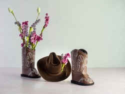 Cowgirl or cowboy brown hat with cowgirl or cowboy brown leather boots with one boot filled with pink and purple artificial flowers and more flowers adorning the hat, cute western fashion apparel.