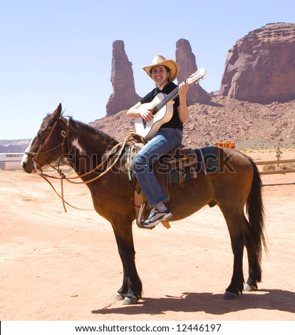 Cowgirl play on guitar. Monument Valley