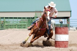 Cowgirl racing her horse between poles during a rodeo.