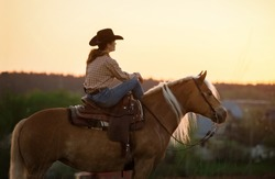 Cowgirl with her horse at sunset