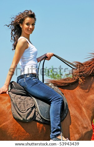 cowgirl - young and attractive woman riding brown horse - stock photo