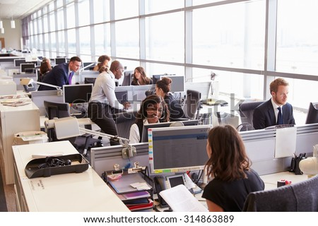 Coworkers at their desks in a busy, open plan office