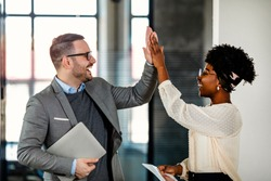 Coworkers celebrating achievement at office. Celebrating success. Happy young man standing in office and giving high five to his colleagues. Two business people high-five. Job well done