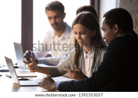 Coworkers having busy workday focus on female chatting with african intern help explain new employee corporate application use pc prepare report make presentation. Teamwork coworking mentoring concept #1395353057