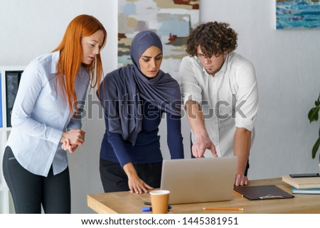 Coworkers present a project to their boss. Muslim business woman looking at a laptop attentively and giving feedback.