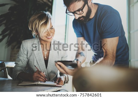 Coworkers working process at home.Young blonde woman working together with bearded colleague man at modern home office.People using electronic devices.Blurred background.Horizontal