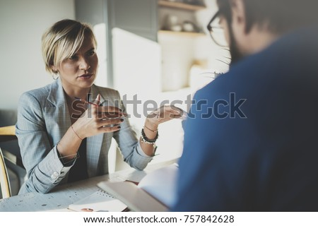 Coworkers working process at home.Young blonde woman working together with bearded colleague man at modern home office.People making conversation together.Blurred background.Horizontal