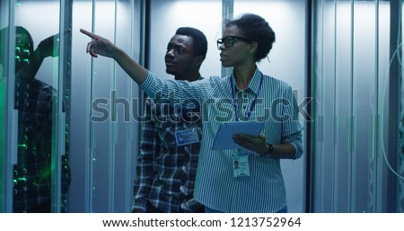 Coworking African American man and woman with tablet walking in corridor with server racks checking hardware in team