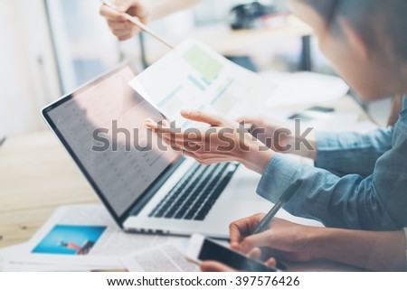 Coworking team.Closeup photo young business managers  working with new startup project in office.Analyze document,statistics plans screen. Notebook on wood table,papers,documents. Horizontal, blurred
