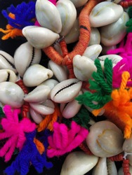 Cowrie shells along with colorful tassels detailed shot