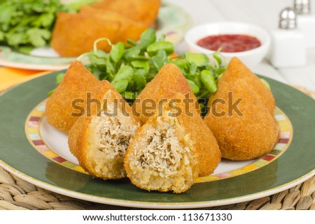 Coxinha de Galinha - Brazilian breaded and deep fried snack filled with shredded chicken served with chili dip. Rissoles on the background.