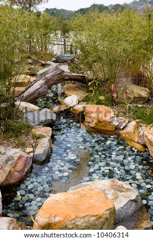 stock photo Coy fish pond with rocks and vegetation