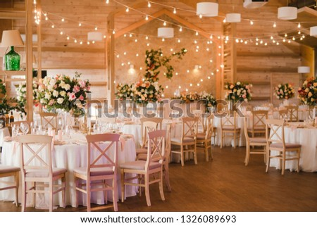 Coziness and style. Modern event design. Table setting at wedding reception. Floral compositions with beautiful flowers and greenery, candles, laying and plates on decorated table. #1326089693