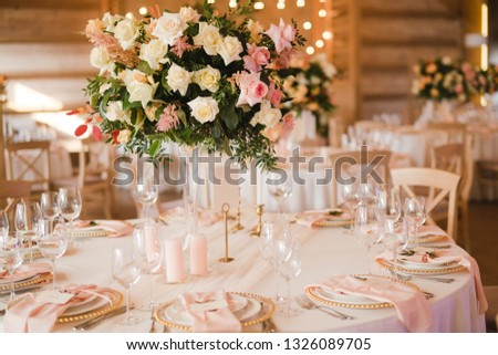Coziness and style. Modern event design. Table setting at wedding reception. Floral compositions with beautiful flowers and greenery, candles, laying and plates on decorated table. #1326089705