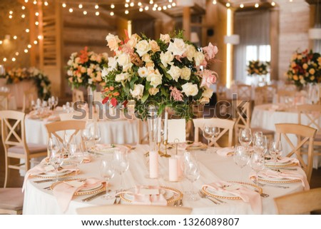 Coziness and style. Modern event design. Table setting at wedding reception. Floral compositions with beautiful flowers and greenery, candles, laying and plates on decorated table. #1326089807