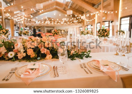Coziness and style. Modern event design. Table setting at wedding reception. Floral compositions with beautiful flowers and greenery, candles, laying and plates on decorated table. #1326089825