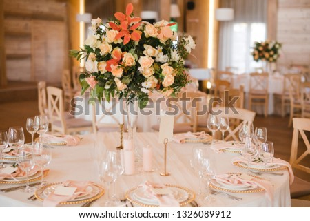 Coziness and style. Modern event design. Table setting at wedding reception. Floral compositions with beautiful flowers and greenery, candles, laying and plates on decorated table. #1326089912